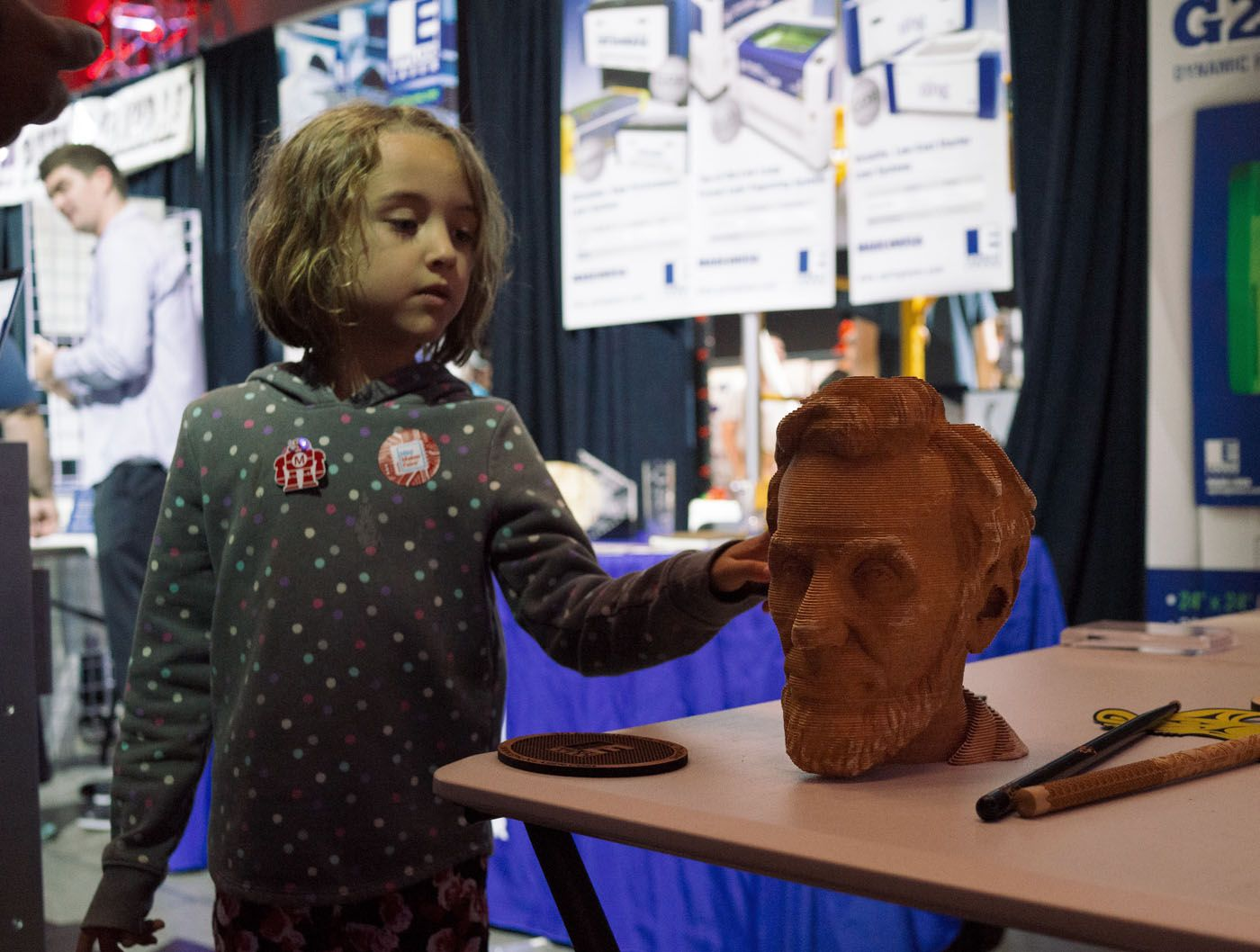 A girl checks out a3D-printed bust of Abraham Lincoln. This print is special because it uses multiple axes.
