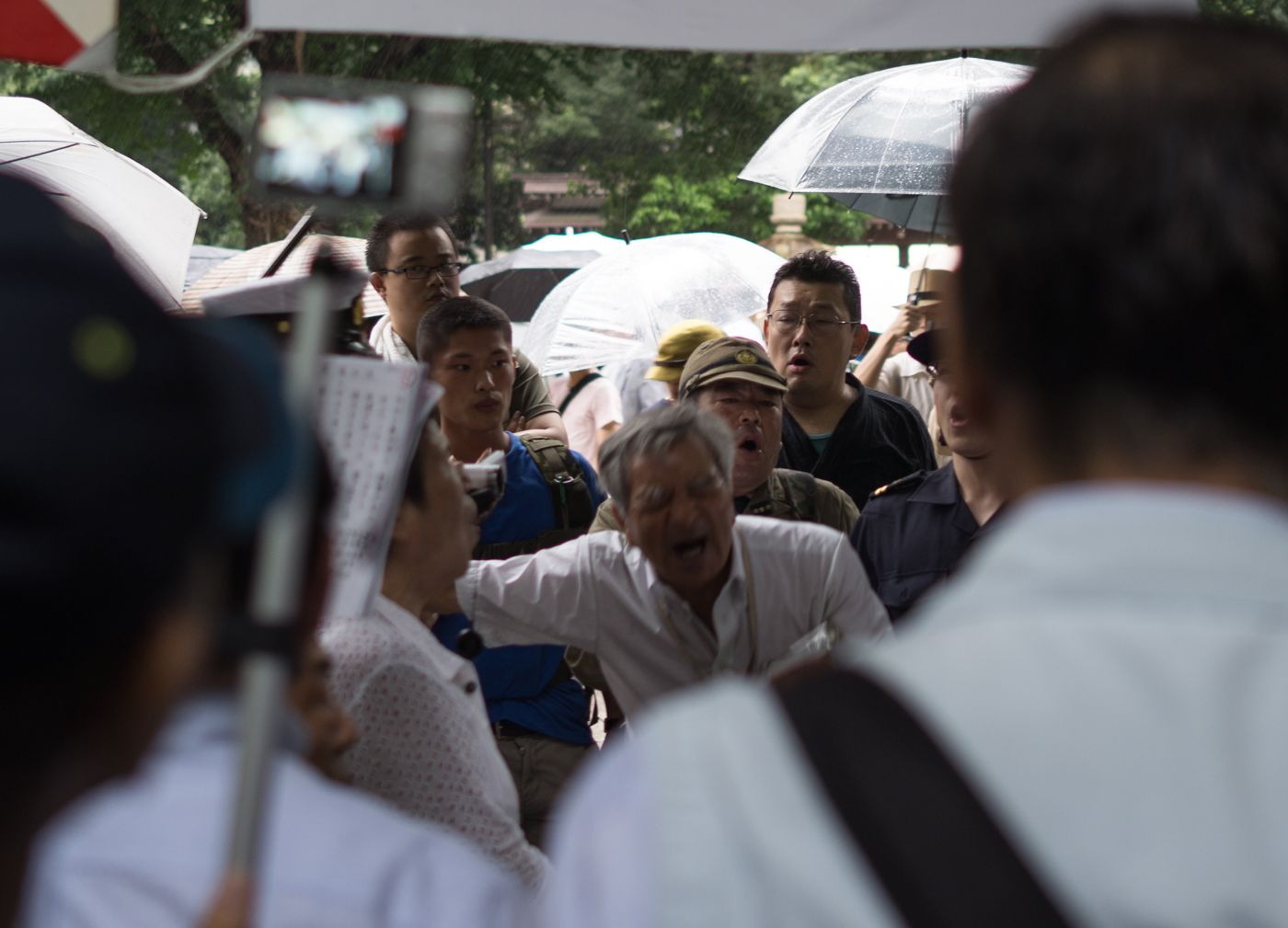 Man in white passionately leads nationalists and sympathetic onlookers in song.
