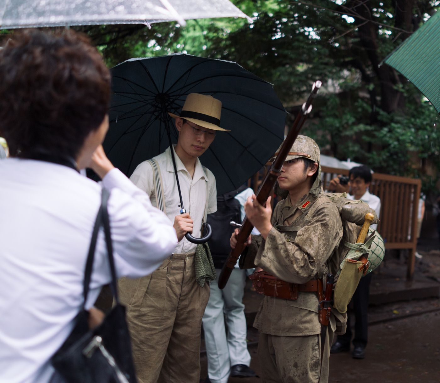 A grandma asks a teenager, dressed in an Imperial Japan uniform, to take a photo with her grandson (not pictured).